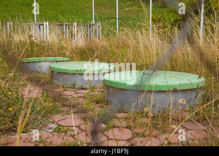 View of septic tanks through a fence behind a commercial building, Donovaly village, Slovakia, Europe - Stock Photo