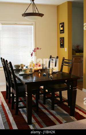 Dining table and plates on a dining table (note: pics on the wall are mine) - Stock Photo