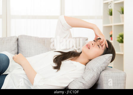 Young woman with headache lying on couch at home. casual style indoor shoot. lifestyle and health concept mixed - Stock Photo