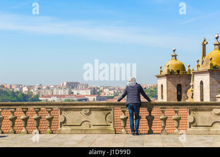 A man stands alone on the terrace of the cathedral in Porto, Portugal, looking over the rooftops of the old town - Stock Photo