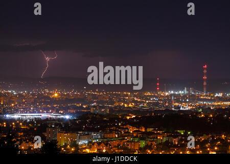 Lightning storm over city skyline at night. Kielce, Poland, Holy Cross Mountains. - Stock Photo