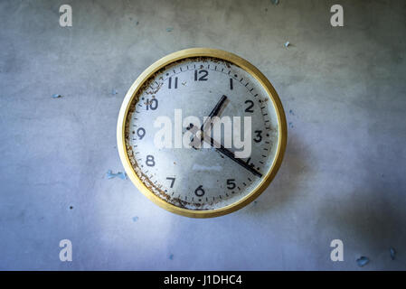 Old clock in abandoned Jupiter Factory in Pripyat ghost town of Chernobyl Nuclear Power Plant Zone of Alienation - Stock Photo