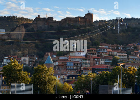 View on cableway under roof of houses Old city at sunset. Tbilisi, Georgia - Stock Photo