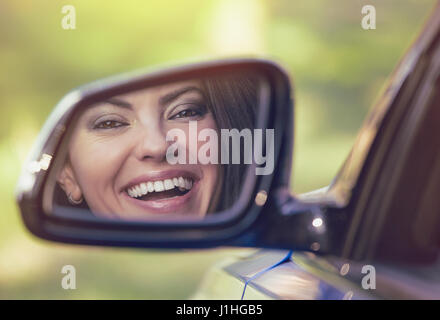 Happy young woman driver looking in car side view mirror, making sure lane is free before making a turn. Positive - Stock Photo