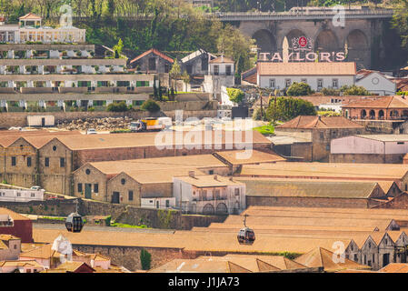 Porto Portugal Gaia, cable cars carrying tourists pass over the rooftops of port wine lodges sited in the waterfront - Stock Photo