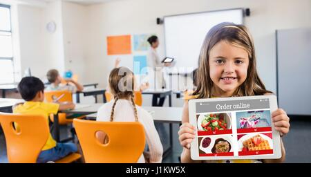 Digital composite of Happy girl holding digital tablet with restaurant site on screen in classroom - Stock Photo