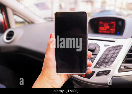 Close up Young female driver using touch screen smartphone and gps navigation in a car, concept using smart phone - Stock Photo
