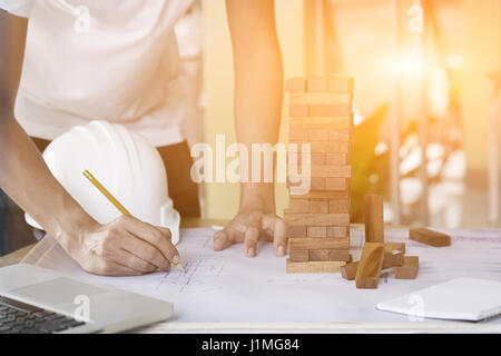 Projecting with pencil on the big urban drawings. Town planning and wood tower model for a architecture,architect - Stock Photo