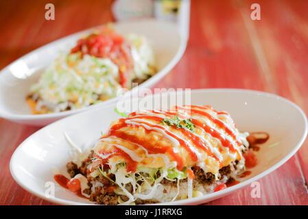 Okonomiyaki Japanese pancakes on white dish - Stock Photo