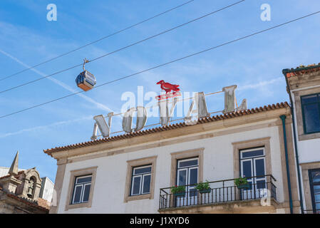 Porto Portugal Gaia, a cable car carrying tourists passes over a Noval Port sign in the waterfront Gaia district - Stock Photo