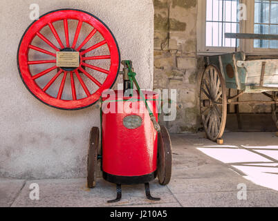 Old restored red wheel from steam powered fire engine, water pump, and old cart, Penicuik House, Midlothian, Scotland, - Stock Photo