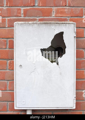 a meter box broken into outside with cracked dent hole old danger electric gas box on brick wall on house crime - Stock Photo