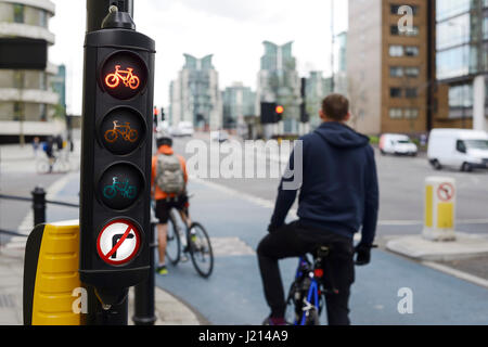 Cyclists wait at the red traffic light for a bike lane in central London UK - Stock Photo