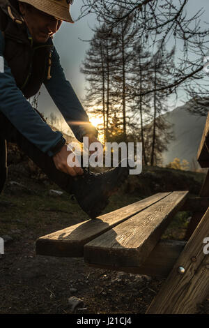 A man adjusting his hiking boots to go for a mountain hike as the sunrise or sunset in the mountains alpine landscape - Stock Photo