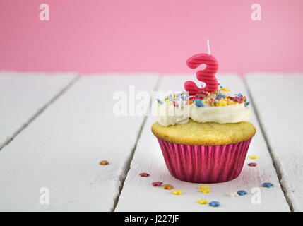 Happy birthday cup cake with star sprinkles and number 3 pink candle on white table with pink background - Birthday - Stock Photo