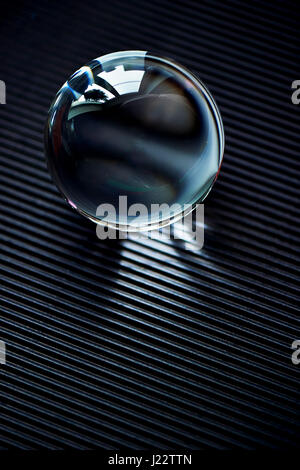 Glass globe or drop of water on a dark graphite corrugated paper . Clean and Shine - Stock Photo