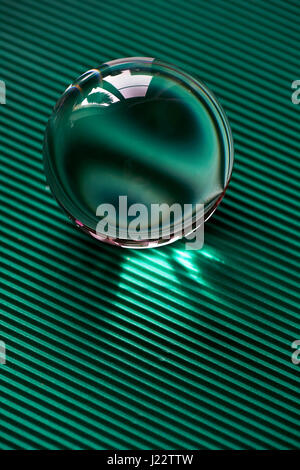 Glass globe or drop of water on a background of green corrugated paper . Clean and Shine - Stock Photo