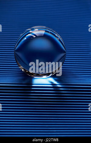 Glass globe or drop of water on a background of blue corrugated paper . Clean and Shine - Stock Photo