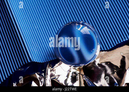 Glass globe or drop of water on a background of blue corrugated paper and foil . Clean and Shine - Stock Photo