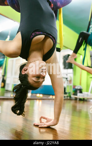 Woman practicing aerial yoga in class - Stock Photo