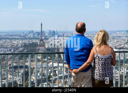Couple on the observation deck at the top of the Tour Montparnasse, looking towards the Eiffel Tower and La Defense, - Stock Photo