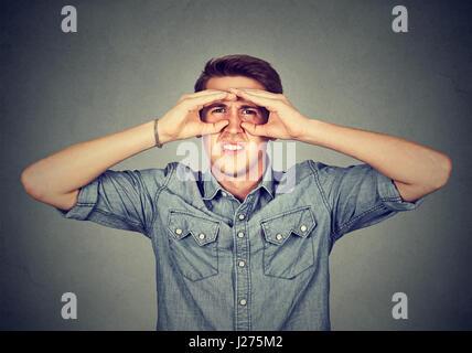 Displeased young man looking through fingers like binoculars - Stock Photo