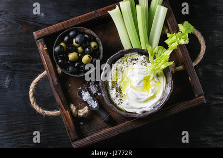 Fresh celery with yogurt and olive oil dip in ceramic bowl, served with sea salt and black, green olives on wood - Stock Photo