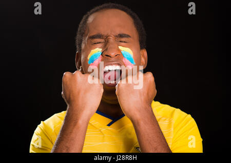 Quito, Ecuador - May 25, 2016: Headshot dark skinned male wearing yellow ecuadorian football shirt in front of black - Stock Photo