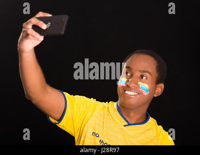 Quito, Ecuador - May 25, 2016: Headshot dark skinned male wearing Ecuadorian yellow football shirt in front of black - Stock Photo