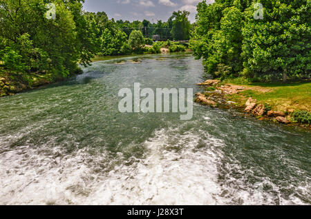 Headwater of the Spring River in Missouri as it flows from a dam toward a bridge - Stock Photo