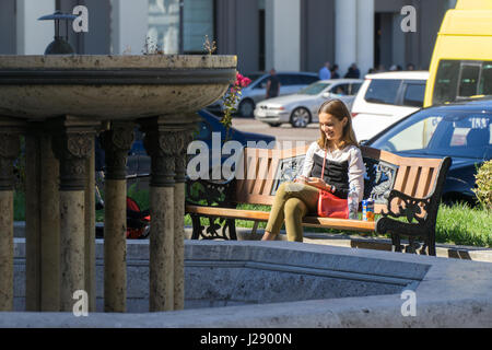 TBILISI, GEORGIA-SEP 25, 2016: Girl with telephone sitting on a bench in Liberty square. - Stock Photo
