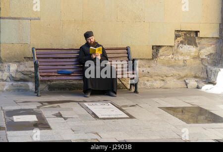 TBILISI, GEORGIA-SEP 25, 2016: Georgian priest reading a book sitting on a bench - Stock Photo