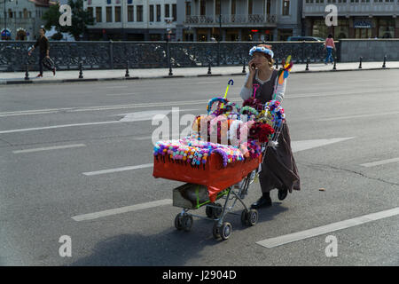TBILISI, GEORGIA-SEP 25, 2016: Saleswoman of the wreaths is on the road pushing a shopping trolley with goods. - Stock Photo