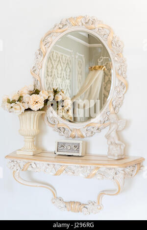 Luxury bedroom wall in light colors with mirror. Elegant classic interior - Stock Photo
