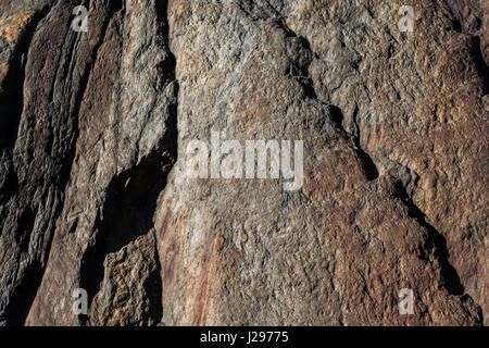 Detail of granite rock with traces of red iron in surface weathered and with signs of erosion - Stock Photo