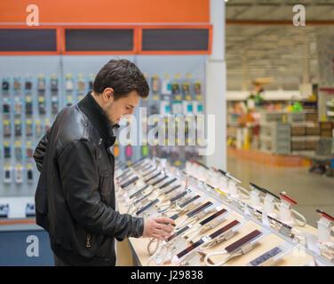 young male customer choosing smartphone - Stock Photo