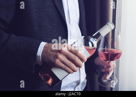 Horizontal close up of Caucasian man in black suit and white shirt pouring rose wine into a tall glass from a bottle - Stock Photo