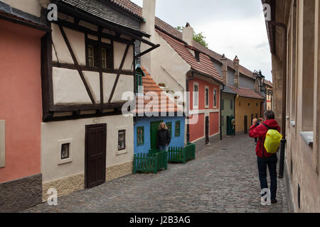 Tourists take photographs using a smartphone in front of the tiny medieval house number 19 in Golden Line in Prague - Stock Photo