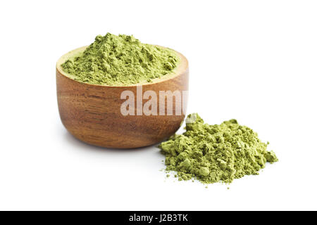 Green matcha tea powder in wooden bowl isolated on white background. - Stock Photo