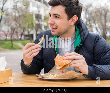 man eating a burger with fried potatoes in street food cafe - Stock Photo