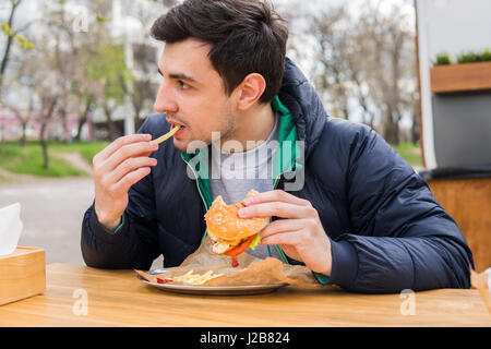 man eating fried potatoes with a burger in street food cafe - Stock Photo