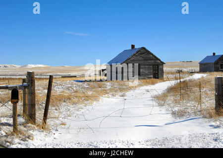 Snowy path leads to abandoned farm house and outbuilding.  Rustic wooden fence bars entry.  Mailbox hangs empty - Stock Photo