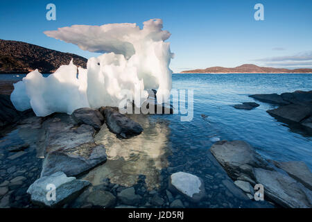 Canada, Nunavut Territory, Setting midnight sun lights melting iceberg stranded at low tide in Frozen Channel at - Stock Photo