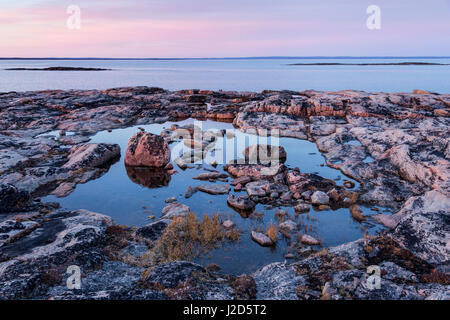 Canada, Nunavut, Territory, Setting midnight sun lights clouds above rocky coastline of Harbour Islands along Hudson - Stock Photo
