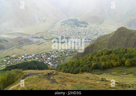 Top view of village Stepantsminda from Gergeti Trinity Church in september, Georgia - Stock Photo