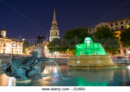 Water fountain and water sculpture in Trafalgar Square with St Martin-in-the-Fields church in the background at - Stock Photo