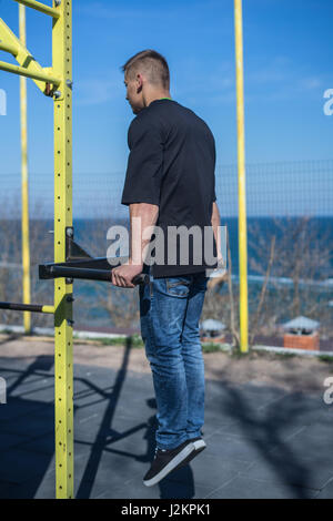 Young Athlete doing a Hand Stand On Parallel Bars In An Outdoor Gym - Stock Photo