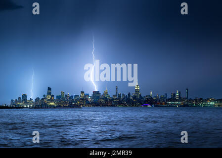 Lightning striking New York City skyscrapers at night. Stormy skies over Midtown West Manhattan from the Hudson - Stock Photo