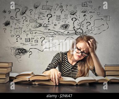 Confused woman studying inside - Stock Photo