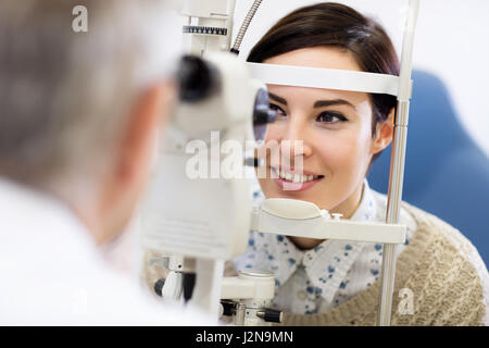 Dark hear woman look in ophthalmoscope to determine diopter in clinic - Stock Photo